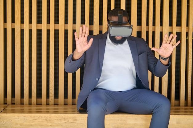 Un hombre de piel oscura con gafas de realidad virtual que parece entretenido