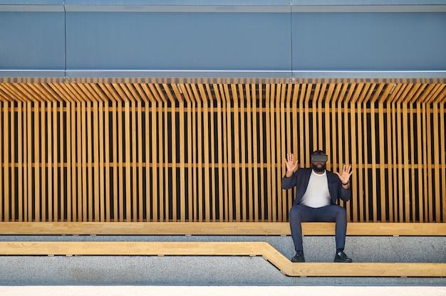 Un hombre de piel oscura con gafas de realidad virtual sentado en el banco