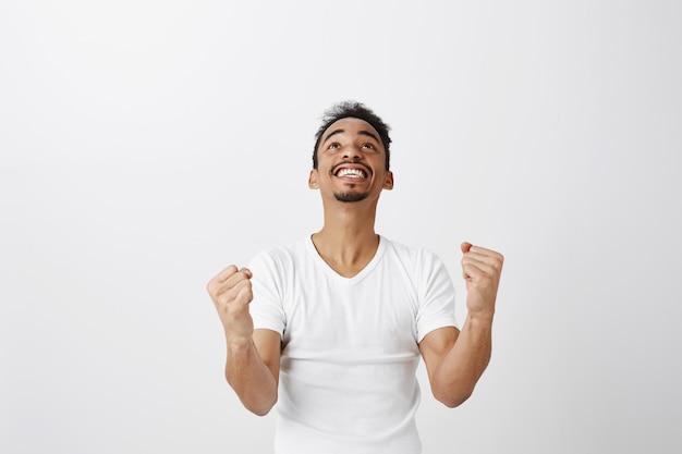 Hombre de piel oscura ganador exitoso regocijándose, puñetazo y sonriendo, diciendo que sí, triunfando