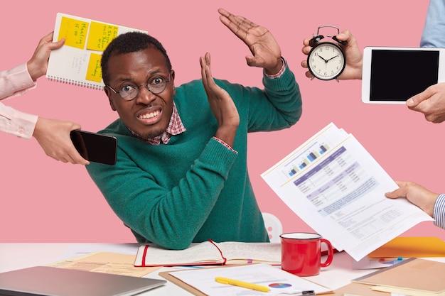 Hombre de piel oscura molesto y disgustado se niega a trabajar, hace un gesto de parada, diferentes personas sostienen el despertador, el panel táctil