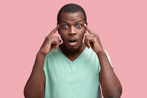 El hombre de piel oscura con ojos saltones mira con expresión frustrada y sorprendida, mantiene los dedos en las sienes, trata de recordar la respuesta correcta, aislado sobre estudio rosa