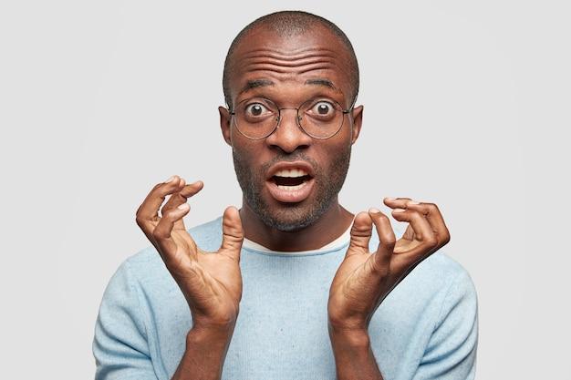 El hombre de piel oscura reacciona ante noticias repentinas, mantiene las manos cerca de la cara, tiene una expresión facial sorprendida