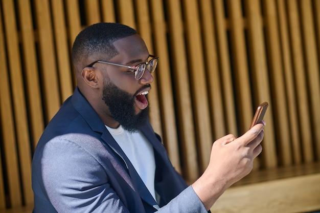 Un hombre de piel oscura con un traje sentado en el banco con un teléfono inteligente en las manos