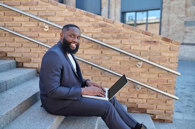 Un hombre de piel oscura con un traje sentado en los escalones con una computadora portátil