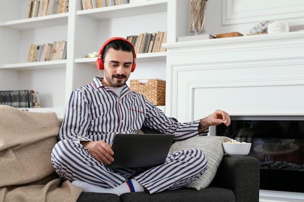 Hombre en pijama pasar tiempo divertido en la computadora portátil