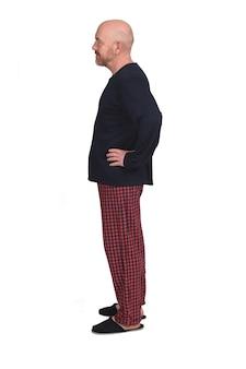 Hombre en pijama sobre fondo blanco, manos en la cadera, perfil