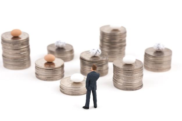 Hombre con pilas de monedas en blanco