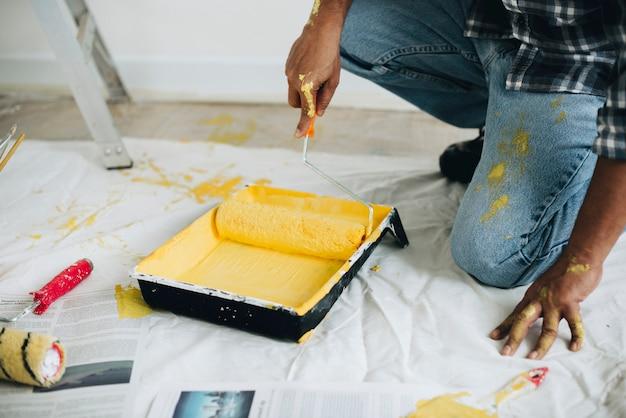 Hombre pintando las paredes amarillas.