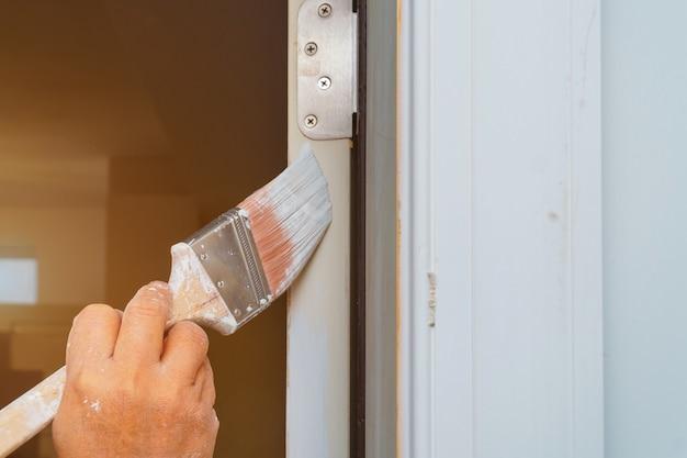 El hombre está pintando puerta con pincel.