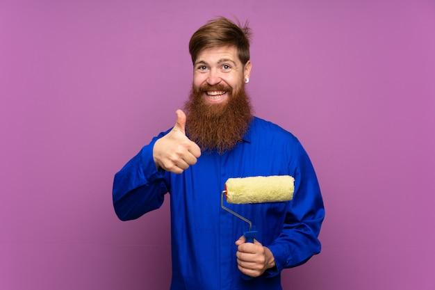 Hombre pintor con barba larga dando un gesto de pulgares arriba