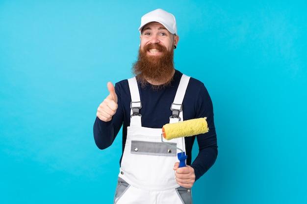 Hombre pintor con barba larga sobre pared azul aislado dando un gesto de pulgares arriba