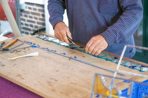 Hombre pintor hace vidrieras.