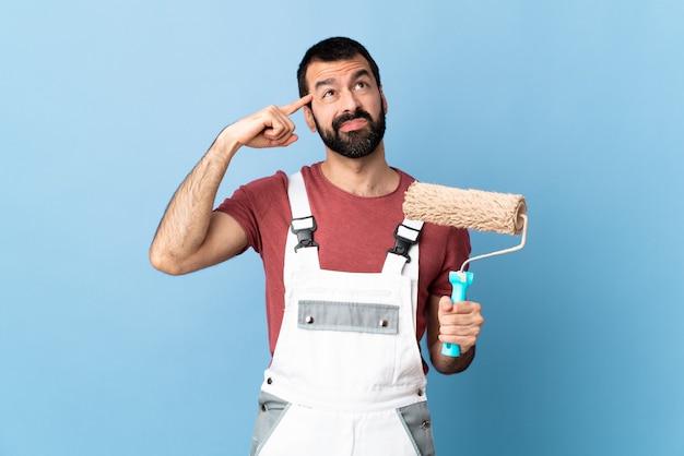 Hombre pintor en pared pastel