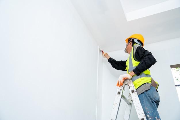 Hombre pintor pintando la pared en un edificio sin terminar, con pincel, aislado en un gran espacio vacío con escalera de madera en el sitio de construcción