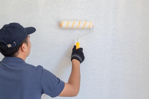 Hombre pintor en el trabajo con un rodillo de pintura en la pared