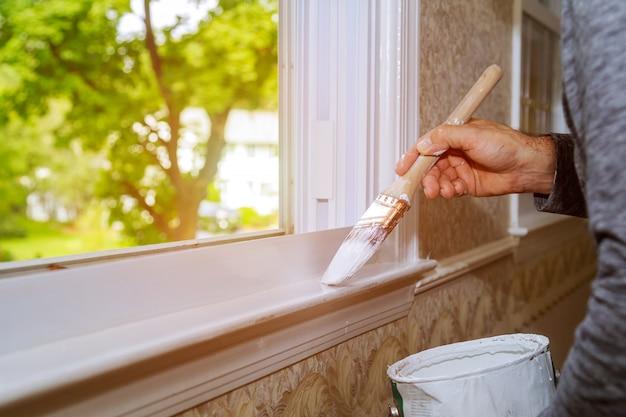 Hombre pintura ventana recortar en casa, primer plano