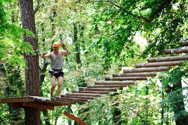 Hombre pisa en los bloques de madera que cuelgan en el aire