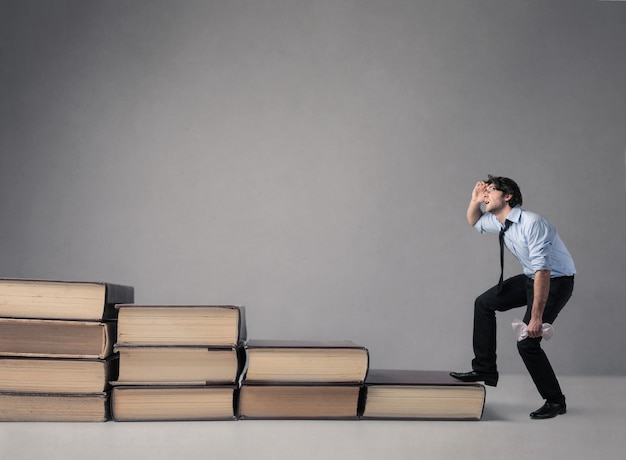 Hombre pisando grandes libros