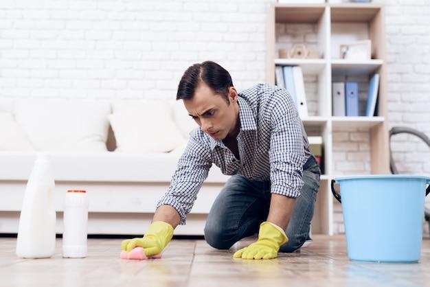 Hombre con el piso de limpieza toallita en el apartamento.
