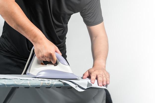 El hombre está planchando la camisa sobre la mesa, las tareas domésticas