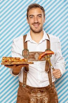 Hombre con plato de madera de salchichas alemanas