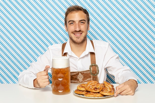 Hombre con plato de pretzels y cerveza