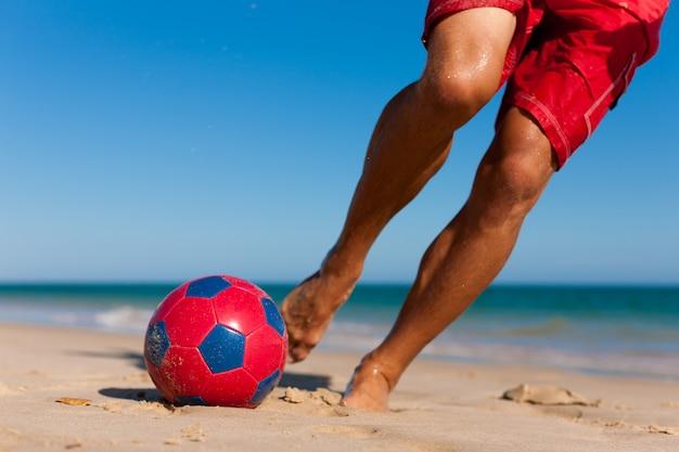 Hombre en la playa jugando al fútbol