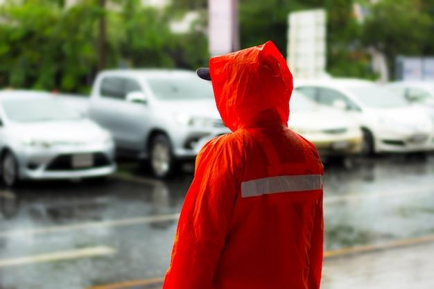 Hombre policía y gabardina naranja soporte medio de la lluvia en el estacionamiento al aire libre