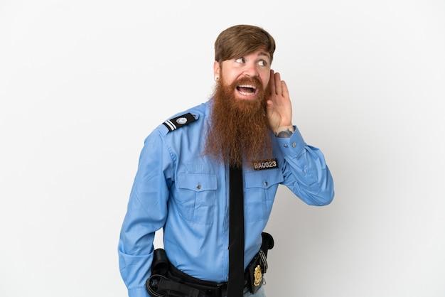 Hombre policía pelirrojo aislado sobre fondo blanco escuchando algo poniendo la mano en la oreja