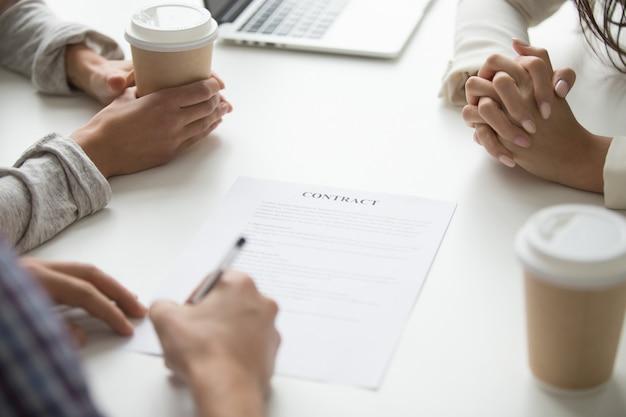 El hombre pone la firma en el contrato, los clientes firman el concepto de documento, primer plano