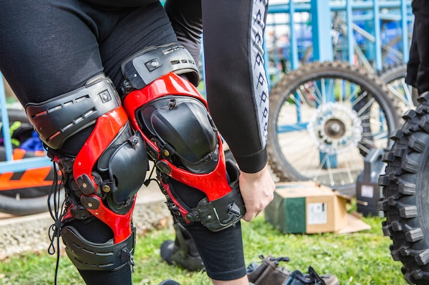 El hombre pone protección de rodillas para el deporte del motor