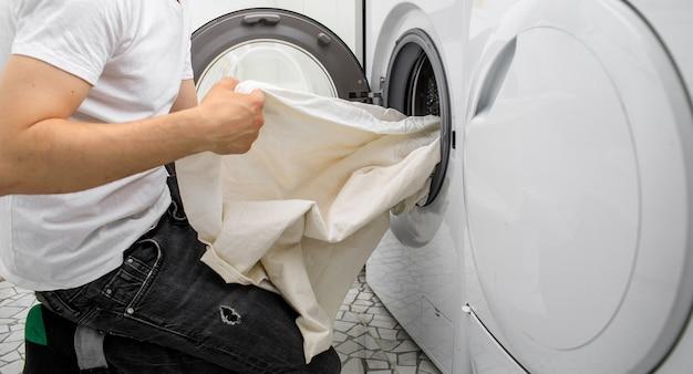El hombre pone la ropa en una lavadora automática