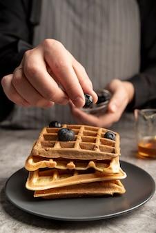 Hombre poniendo arándanos encima de waffles