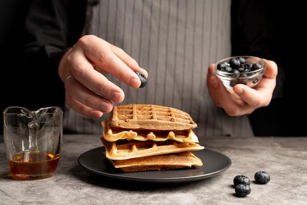Hombre poniendo arándanos en la pila de waffles
