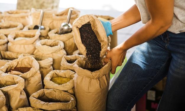 Hombre poniendo arroz negro en una bolsa de papel marrón en una tienda de comestibles