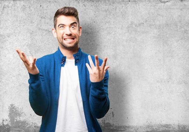 Hombre poniendo una cara extraña y los dedos levantados