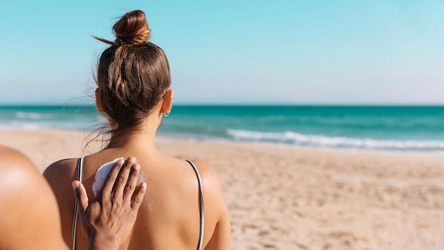 Hombre poniendo crema de sol en la espalda novia en la costa