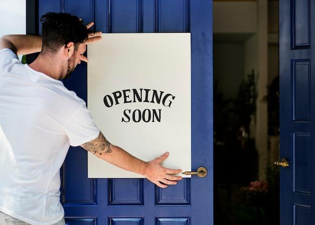 Hombre poniendo en la apertura de la tienda pronto signo