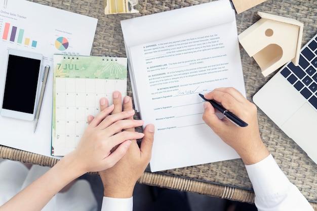 Hombre poniendo la firma en el contrato de préstamo de documentos y sosteniendo las manos pareja
