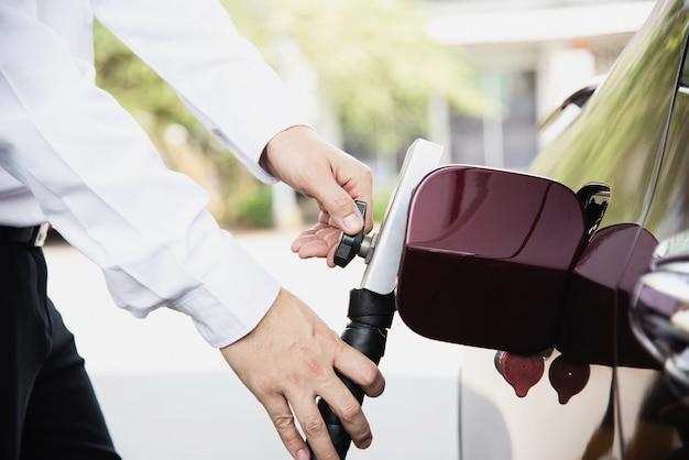 El hombre está poniendo gnv, vehículo de gas natural, dispensador de cabeza a un automóvil en la estación de gasolina en tailandia