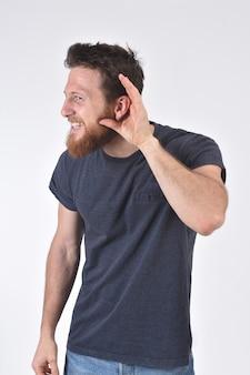 Hombre poniendo una mano sobre su oreja porque no puede escuchar en blanco