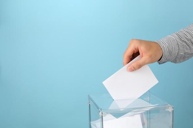 Hombre poniendo papeleta en urna de votación