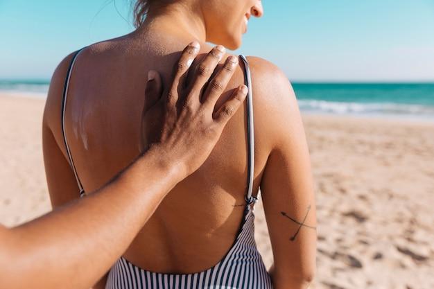 Hombre poniendo protector solar joven mujer curtida por la costa