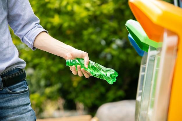 Hombre poniendo retorcida botella de plástico verde en la papelera de reciclaje en el parque.