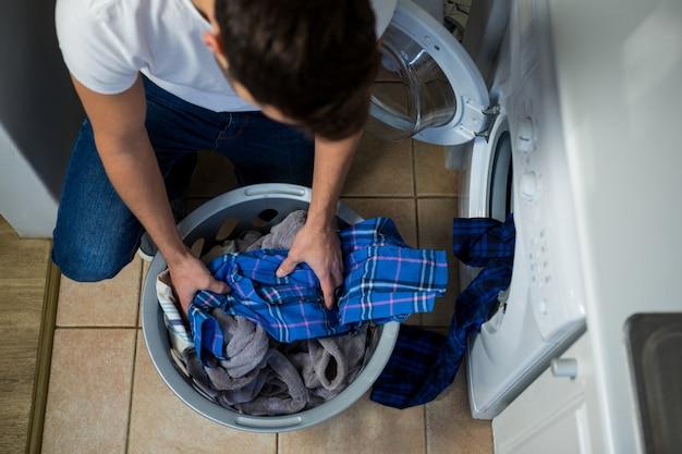 Hombre poniendo ropa sucia en la lavadora