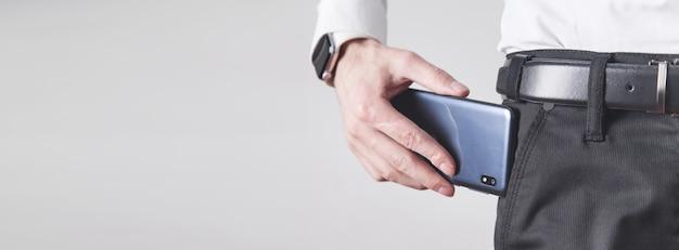 Hombre poniendo smartphone en el bolsillo de los pantalones.