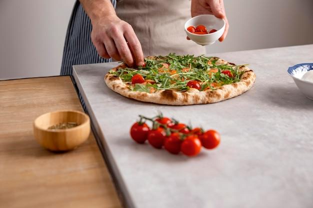 Hombre poniendo tomates en masa de pizza al horno con rodajas de salmón ahumado