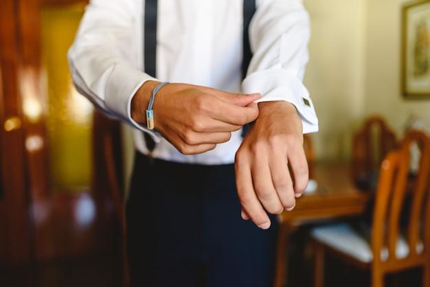 Hombre poniéndose una camisa blanca para vestir elegantemente.