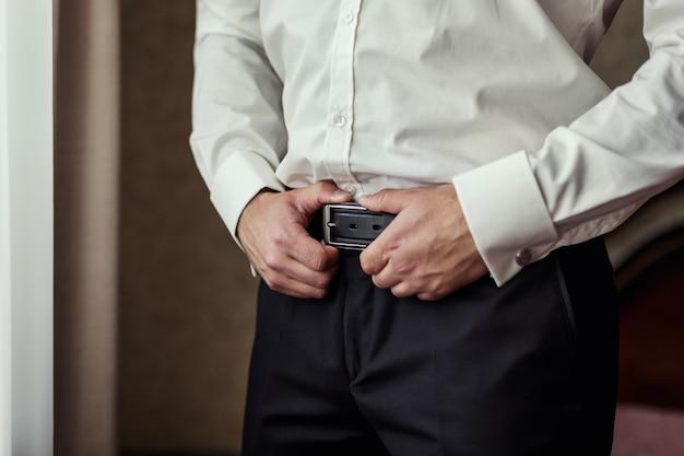 Hombre poniéndose un cinturón, hombre de negocios, político, estilo del hombre, primer plano de manos masculinas, hombre de negocios estadounidense, hombre de negocios europeo, un hombre de negocios de asia, personas, negocios, moda y concepto de ropa