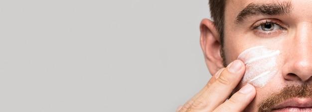 Hombre poniéndose crema facial con espacio de copia